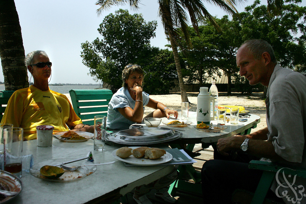 Academy Director Pascal Theault (l) has lunch with his wife and the coach of the professional ASEC team at the ASEC football academy February 16, 2006 in Abidjan, Ivory Coast. ASEC academy has an established history of producing top notch footballers who go on to play in the top European football leagues.