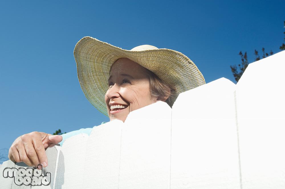 Woman peering over garden fence