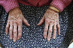 Close up of hands of an elderly woman; resting on her lap,