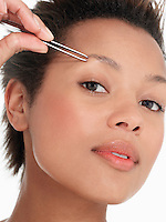 Young Woman plucking Eyebrows close up head shot
