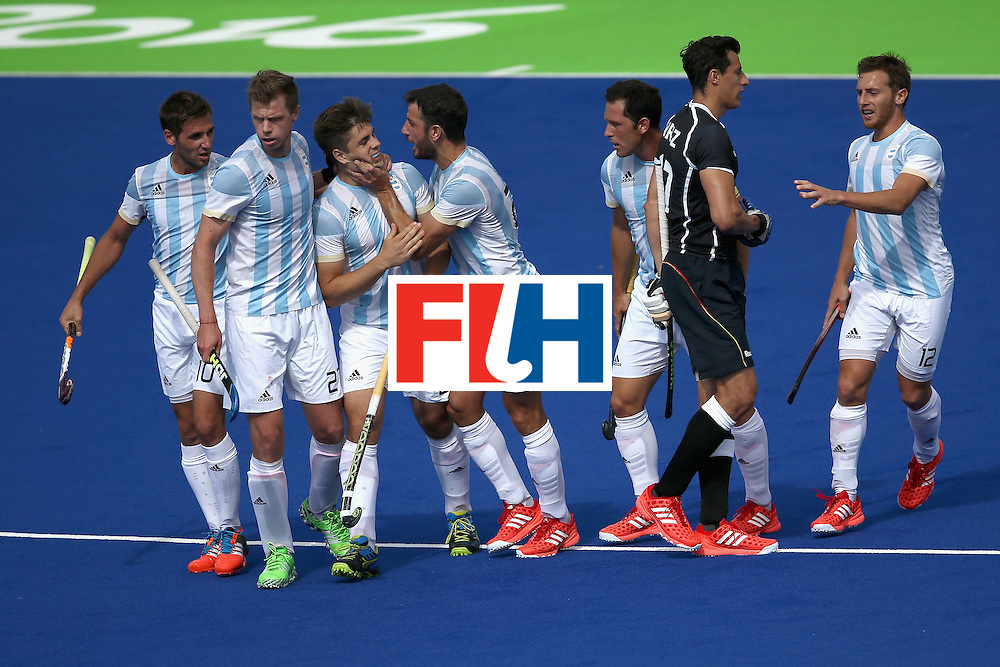 RIO DE JANEIRO, BRAZIL - AUGUST 11:  Timur Oruz #27 of Germany  walks past as Matias Paredes #10, Matias Paredes #10, Pedro Ibarra #5, Lucas Vila #12 of Argentina, and Manuel Brunet #24 of Argentina react to a goal during a Men's Preliminary Pool B match on Day 6 of the Rio 2016 Olympics at the Olympic Hockey Centre on August 11, 2016 in Rio de Janeiro, Brazil.  (Photo by Sean M. Haffey/Getty Images)