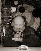 man with grey beard in house cuddling his dog
