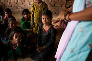 Sundar (center, in black), 8-9 years, kneels amongst other rag-picker's children in class in the Nai Duniya activity center in remote Lodha Basti, Manana village, Samalkha town, Haryana, India on 15th June 2012. Sundar walks 1.5km to and from her rag-picking work each day. Most of these children are rag-pickers themselves. They are now able to go to school from 8-12 in the morning, and study again at the activity center after work at 4pm. A new program to encourage the rag-picker's children to attend school is underway, to keep them from becoming the next generation of rag-pickers in cities. Photo by Suzanne Lee for The National