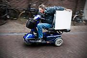 Een man vervoert een wasdroger achterop zijn scootmobiel