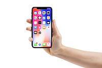 Woman hand holding Apple iPhone X, large screen smartphone, with colorful blue red desktop on its display. The phone is isolated on white background with a clipping path.