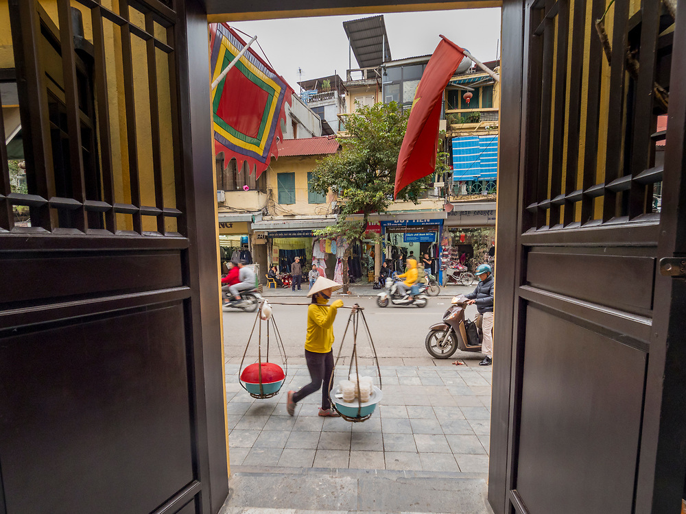 Asia, Vietnam, Hanoi, old quarter, flags and busy street viewed through traditional wooden doors