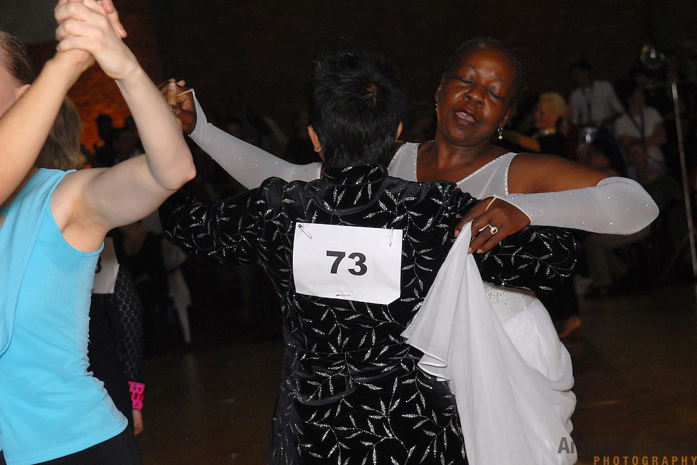 Roke Noir, center, and Sheila Dodd, right, both of Oakland, California, compete in the adult women's standard division of the same-sex ballroom dancing competition during the 2007 Eurogames at the Waagnatie hangar in Antwerp, Belgium on July 14, 2007. ..Over 3,000 LGBT athletes competed in 11 sports, including same-sex dance, during the 11th annual European gay sporting event. Same-sex ballroom is a growing sports that has been happening in Europe for over two decades.