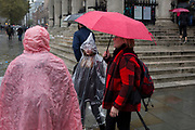 Londoners and visitors to the capital endure heavy rainfall on an autumn afternoon outside St. Martin-in-the-Fields church on Trafalgar Square, on 24th October 2019, in Westminster, London, England.