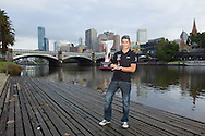 "Craig Alexander (AUS) Pro Male Winner of the inaugural Ironman Melbourne Triathlon with the ""Greg Welch Trothy"" and Melbourne city in the background.Post Race Trophy Shoot. 2012 Ironman Melbourne. Asia-Pacific Championship. 26/03/2012. Photo By Lucas Wroe."