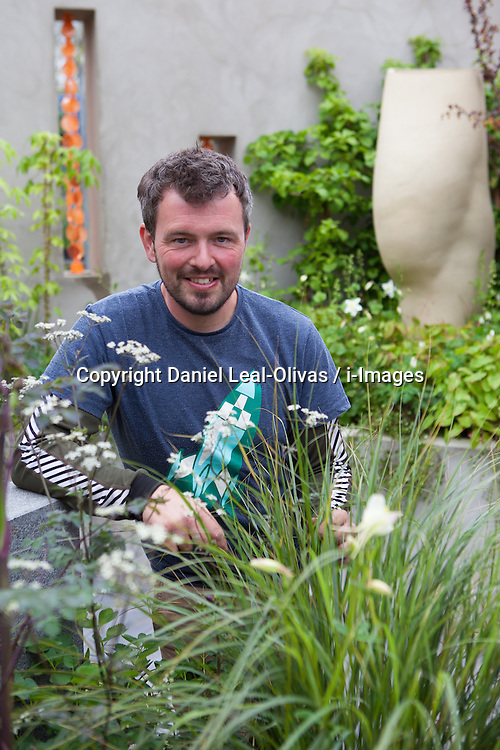 Gardener, Paul Hervey-Brookes doing last minute planting at Chelsea Flower Show. The BrandAlley Garden designed by Paul Hervey-Brookes. at the RHS Chelsea Flower Show, London. The BrandAlley Garden represents a no-compromise expression of our 'public' and 'private' faces, which are so interdependent. The result is a stylish outside room, harmoniously designed as a place to entertain and be seen in, as well as one for sanctuary and reflection, the Chelsea Flower Show, London, UK, Saturday May 18, 2013. Photo by:  Daniel Leal-Olivas / i-Images