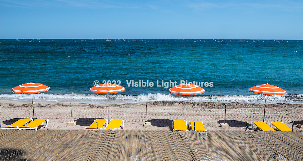 "Orange beach umbrellas on the shore at Cap Ferrat in the South of France.  This is a cropped version of the original aspect image in the ""South of France"" gallery on this site.  I've printed this one directly on brushed aluminum and it looks spectacular!  Metal and acrylic prints are specialty items that can be requested, but are not available directly from the check-out section of this site.  Please contact me for more information, pricing, etc."