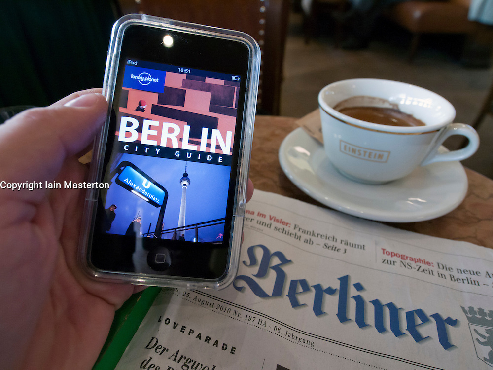 Tourist using e-book guide to Berlin in famous Cafe Einstein on Unter den Linden in Mitte Berlin Germany