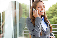 Beautiful businesswoman using cell phone by glass door