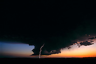 Nebraska Sandhills.  Shortly after sunset, a bolt of lightning is sent from a wall cloud, as an immense thunderstorm looms on the western horizon. Thunderstorms in the High Plains region are commonplace because this is where colder dryer air masses from the north and west, and warmer, moister air masses from the south collide.