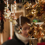 VERONA, ITALY - DECEMBER 04:  A stall holder sells Christmas decorations in a wodden hut at the Verona Christmas Market on December 4, 2010 in Verona, Italy. Christmas markets, fairs, lights and nativity scenes fill Northern Italian cities and villages from December through January 6.