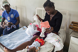 Cherline Pierre, 24, selects clothes for her baby girl at MSF's Centre de Référence en Urgence Obstétricale (CRUO) in Port-au-Prince, Haiti, October 18, 2015. She came in the hospital with 8 centimeters dilation and was admitted due to her high blood pressure.