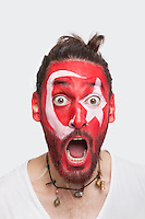 Portrait of shocked young man with Turkish flag painted on face screaming against white background