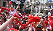 "People wave the traditional red scarves as they celebrate the ""Chupinazo"", the fireworks with whose explosion the San Fermin festivities start, on July 6, 2008, in Pamplona, north of Spain. A man jumps from the Navarreria fountain to fall on the crowd celebrating the ""Chupinazo"", the fireworks with whose explosion the San Fermin festivities start, on July 6, 2008, in Pamplona, north of Spain."