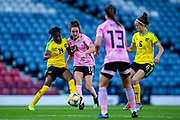 Lisa Evans (#11) of Scotland passes the ball in the direction of Jane Ross (#13) of Scotland as she is closed down by Den-Den Blackwood (#14) of Jamaica during the International Friendly match between Scotland Women and Jamaica Women at Hampden Park, Glasgow, United Kingdom on 28 May 2019.