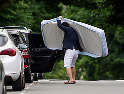 © Licensed to London News Pictures. 24/06/2017. London, UK. A man puts a mattress in his car as residents are evacuated from the Taplow block on the Chalcots Estate in Camden after it failed a fire inspection because of combustable cladding. More than 700 flats in tower blocks on an estate in the Swiss Cottage area of north-west London are being evacuated because of fire safety concerns. Photo credit: Ben Cawthra/LNP