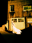 Woman in Wedding Dress Blurs by in an Alley