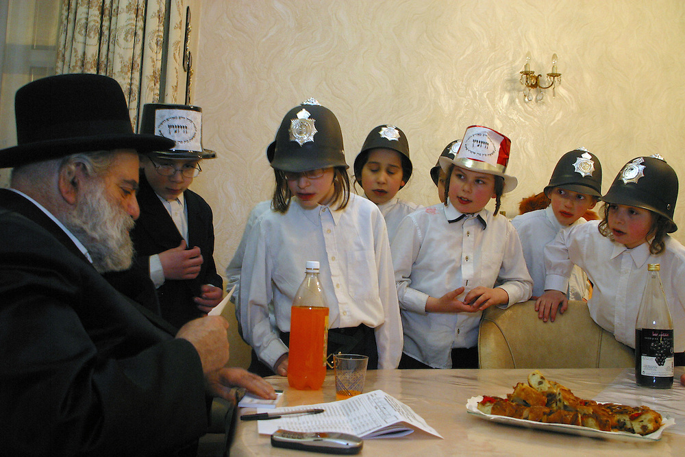 Young Orthodox Jewish boys in fancy dress collecting for their school (Yeshiva) wait in anticipation of the amount they will receive during a visit to the house of Mr Glick, a well off man of the area. Purim is one of the most entertaining Jewish holidays.  It commemorates the time when the Jewish people living in Persia were saved from extermination from a massacre by Haman. Due to the courage of a young Jewish woman called Esther. It is customary to hold carnival-like celebrations on Purim, and for groups of men to go round on the back of lorries and in open top buses visiting local wealthy men, collecting for their charity. It is stated that the men should drink so much alcohol that they don't know the difference between right and wrong.