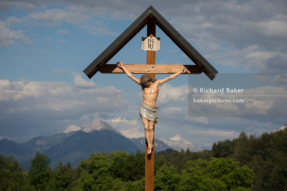 A crucifix looks down on headstones in a rural Slovenian village church, on 18th June 2018, in Bohinjska Bela, Bled, Slovenia.
