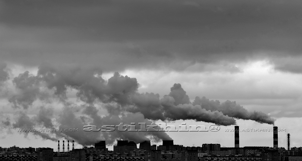 Pipes with a smoke on a background of the sky above city.