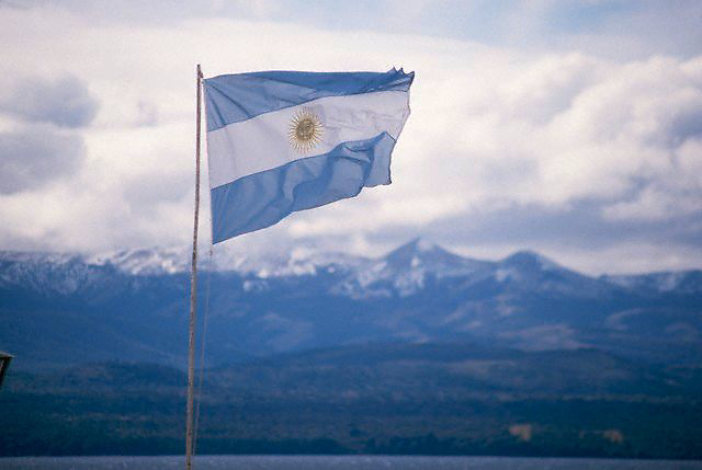 April 1986, Bariloche, Argentina --- An Argentine flag waves in the wind in the Andes town of Bariloche.  The snow capped mountains loom across a lake.   Argentina. --- Image by © Owen Franken/CORBIS