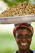 A woman carries a large plate of peanuts on her head while offering them for sale in Kpong, Ghana on Wednesday June 17, 2009.