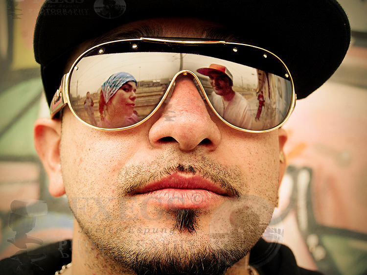 Portrait of three rappers, two of them reflected on the sunglasses of the other