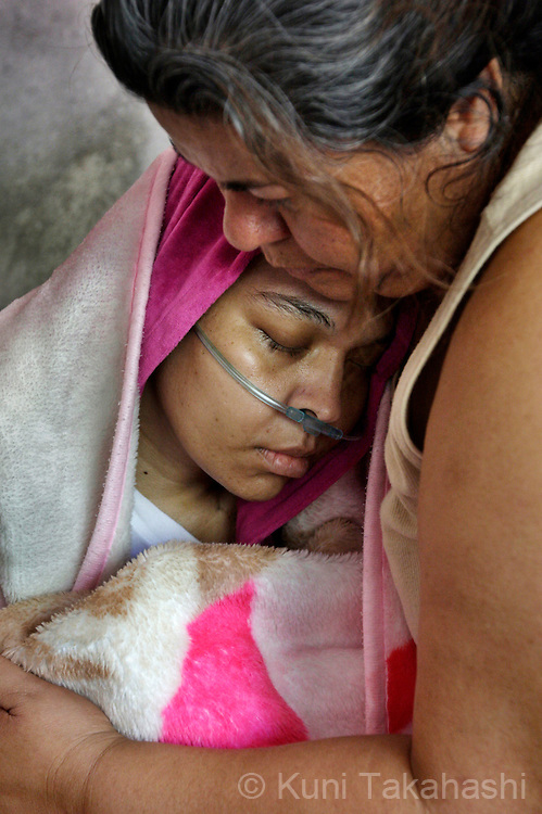 Mariana de la Torre, 29, is comforted by her mother Maria Elena on her bed at her house in Apatzingan, Mexico on March 9, 2009.<br /> (Photo by Kuni Takahashi)