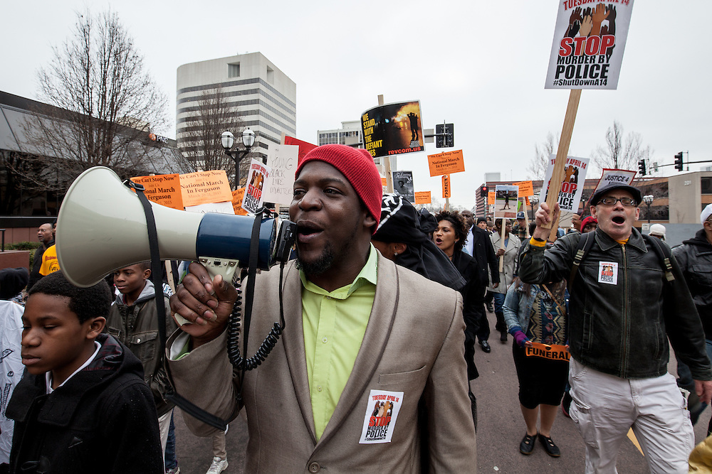 Pastor DERRICK ROBINSON uses a megaphone to lead protestor chants during today's march through Clayton, Missouri.