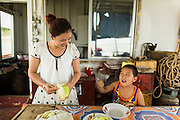 24 APRIL 2014 - CHIANG SAEN, CHIANG RAI, THAILAND: A woman and her son, passengers on a Chinese cargo boat bound for Kunming in China cut up fruit for their lunch. Chinese businesses play an increasingly important role in the Chiang Rai economy. Consumer goods made in China are shipped to Thailand while agricultural products made in Thailand are shipped to China. Large Chinese cargo boats ply the Mekong River as far south as Chiang Saen in the dry season and Chiang Khong when river levels go up in the rainy season.    PHOTO BY JACK KURTZ