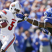 U of L quarterback Teddy Bridgewater is pressured by UK defensive end Alvin Dupree in the first quarter as the University of Kentucky plays the University of Louisville at Commonwealth Stadium in Lexington, Ky. Saturday Sept. 14, 2013. Photo by David Stephenson