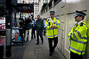 Policemen guarding at a busstation in central London on Friday July 8, 2005 in London, England. One day after the bombings on three subway trains and one bus in London on Juli 7 2005