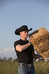 hot rugged cowboy working on a ranch with hay bales