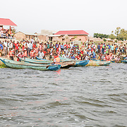 CAPTION: A crowd forms on the shore of Lake Kyoga, and develops a state of high anticipation as boatmen prepare to race each other. With the support of World Renew, the PAG church in Kaberamaido began organizing races like this one as a means of drawing villagers to one place, where they could then get them tested and sensitized on HIV/AIDS. LOCATION: Lake Kyoga, Abrepoli, Kaberamaido District, Uganda. INDIVIDUAL(S) PHOTOGRAPHED: N/A.