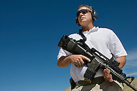 Man holding machine gun at firing range, low angle view