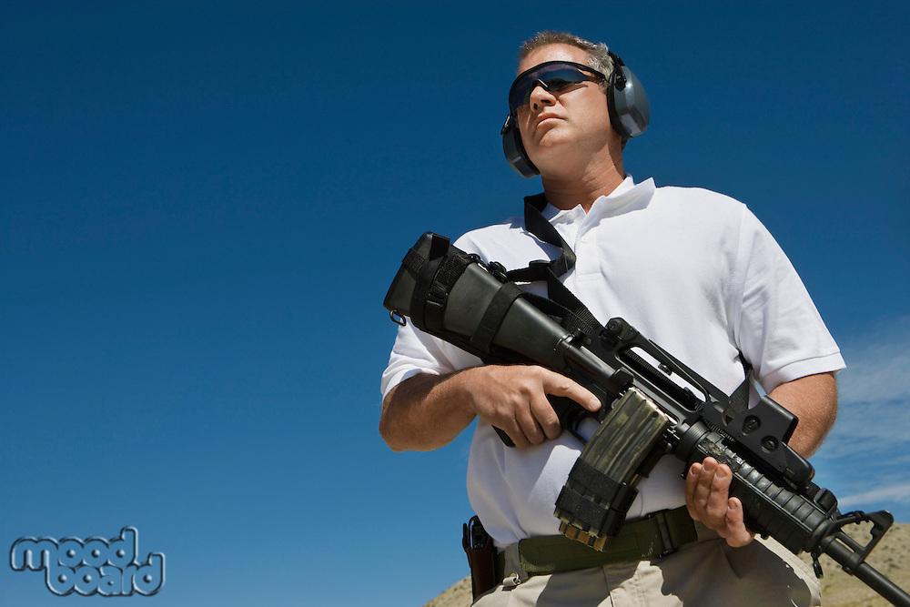 Man holding machine gun at firing range, low angle view