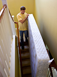 A homeowner moves out a mattress down the stairs of his home in Vallejo, Calif.  He lost his home in 2009 to foreclosure due to a combination of job loss, adjustable loan payments doubling and  home value under water nearly fifty percent. Photo by Kim Kulish