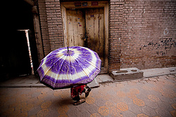 A picture made available on 27 May 2013 of a girl with an umbrella walking along a partly demolished section of the old town of Kashgar, the western edge of China's Xinjiang Uighur Autonomous Region, China 26 May 2013. Kashgar old town's historic labyrinth of earthen mud houses are rapidly being demolished and revamped in a massive government plan to transform the city since 2009. The Chinese government, citing unsafe structures and non-compliance with fire and earthquake safety regulations, has razed and rebuilt more than two thirds of the old city by 2012, relocating thousands of its mainly Uighur ethnic minority residents. Uighurs make up about the majority of the 3.9 million people living in the restive region of Kashgar where the north and south silk road met. Tensions between the Uighurs and Han Chinese have been high as they complain of cultural and religious repression and claim that ethnic Chinese migrants enjoy the main benefits of development in the oil-rich but economically backward region.