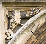 Mythological folklore figure of a griffin dragon carved in stone on the entrance doorway to the church, Peasenhall, Suffolk, England, UK