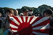 An well-wisher waves a Japanese rising sun flag as Japan's Emperor Akihito (not pictured) appears on a balcony of the Imperial Palace to celebrate his 84th birthday in Tokyo, Japan, December 23, 2017. 23/12/2017-Tokyo, JAPAN