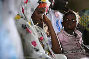 A child sits on her mothers lap during a community meeting with UNICEF Goodwill Ambassador Mia Farrow at the Langui refugee camp outside the town of Garoua, Cameroon on Thursday September 17, 2009.