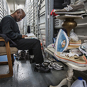 WASHINGTON, DC-OCT14: Wayne Davis, 46, reads the bible in front of his storage unit at Capital Self-Storage, October 14, 2015, in Washington, DC. Davis has been in and out of jail over the years, and also a student at UDC, Many of the area homeless have possessions they want to keep safe, just nowhere permanent to live, so they store their belongings at Capital Self-Storage, where an upper-level unit costs $30/month. Some of the homeless patrons also spend their days in their storage units, when shelters are closed during midday hours. The storage facility near 3rd and Florida Avenue in Northeast, Washington, DC, is about to be replaced by a boutique hotel. (Photo by Evelyn Hockstein/For The Washington Post)