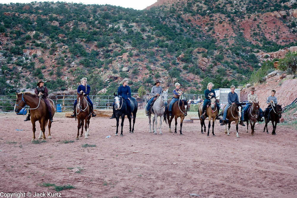 "Aug 9, 2008 -- COLORADO CITY, AZ:   Members of the Jessop family, a polygamist family and members of the FLDS, work with their horses in a corral behind their home in Colorado City, AZ. Colorado City and neighboring town of Hildale, UT, are home to the Fundamentalist Church of Jesus Christ of Latter Day Saints (FLDS) which split from the mainstream Church of Jesus Christ of Latter Day Saints (Mormons) after the Mormons banned plural marriage (polygamy) in 1890 so that Utah could gain statehood into the United States. The FLDS Prophet (leader), Warren Jeffs, has been convicted in Utah of ""rape as an accomplice"" for arranging the marriage of teenage girl to her cousin and is currently on trial for similar, those less serious, charges in Arizona. After Texas child protection authorities raided the Yearning for Zion Ranch, (the FLDS compound in Eldorado, TX) many members of the FLDS community in Colorado City/Hildale fear either Arizona or Utah authorities could raid their homes in the same way. Older members of the community still remember the Short Creek Raid of 1953 when Arizona authorities using National Guard troops, raided the community, arresting the men and placing women and children in ""protective"" custody. After two years in foster care, the women and children returned to their homes. After the raid, the FLDS Church eliminated any connection to the ""Short Creek raid"" by renaming their town Colorado City in Arizona and Hildale in Utah. A member of the Jessop family weeds the community corn plot in Colorado City, AZ. The Jessops are a polygamous family and members of the FLDS. Photo by Jack Kurtz / ZUMA Press"