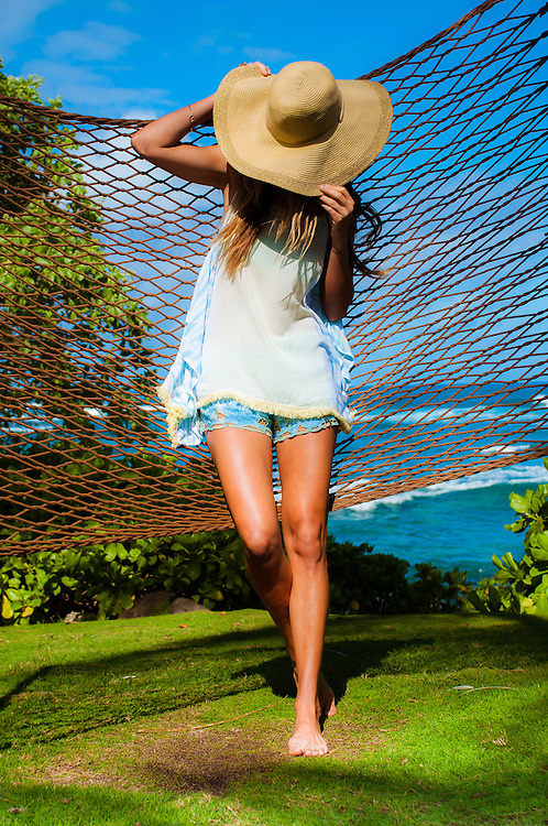 Woman in hammock by the beach at Turtle Bay in Hawaii wearing shorts and tank top by Tiare Hawaii. <br />