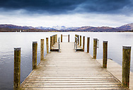 A landing stage on Lake Windermere, with snow-capped hills in the distance.