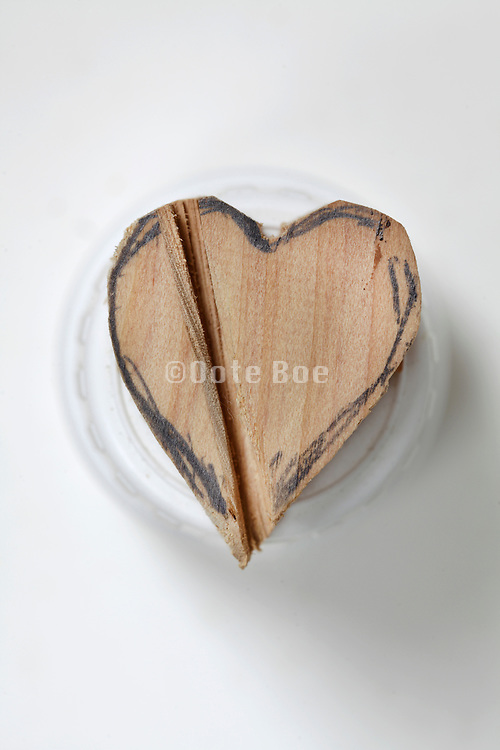 a wooden heart on top of a medicine bottle